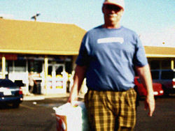 Dr. Malamud outside his neighborhood convenience store with his beer cleverly concealed behind white plastic bags