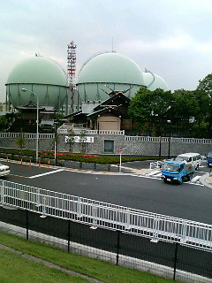 Green gas tanks in the background, historic temple in the foreground