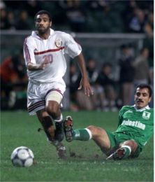 Qatar's Mubarak Mostafa Fazli (L) controls the ball as Palentine's Saeb Jendeya falls.