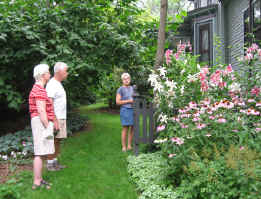 Picture of neighbors touring perennial bed with pink and white lillies, pink cone flowers, astilbe and silvery lamium edging the border