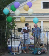 Stragglers enjoy the party as colorful balloons float above