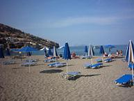 The town beach of Matala with its umbrella's and beachchairs,  and in the distance the islands called Nisia Paximadia.
