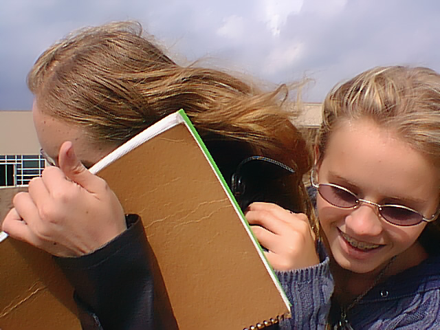 Me hiding behind Dereik�s notebook, while Rachelle tries to get me in a picture